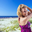 Stock Photo: Womin purple sundress on beach.