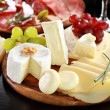 Cheese and salami platter with herbs — Stock Photo
