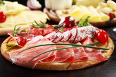 Salami and cheese platter with herbs — Stock Photo