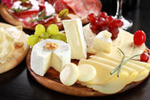Cheese and salami platter with herbs — Stok fotoğraf