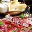 Salami and cheese platter with herbs - Stock Photo