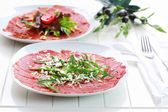 Carpaccio with arugula and cheese — Stock Photo