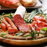 Italian ham and salami with herbs — Stock Photo