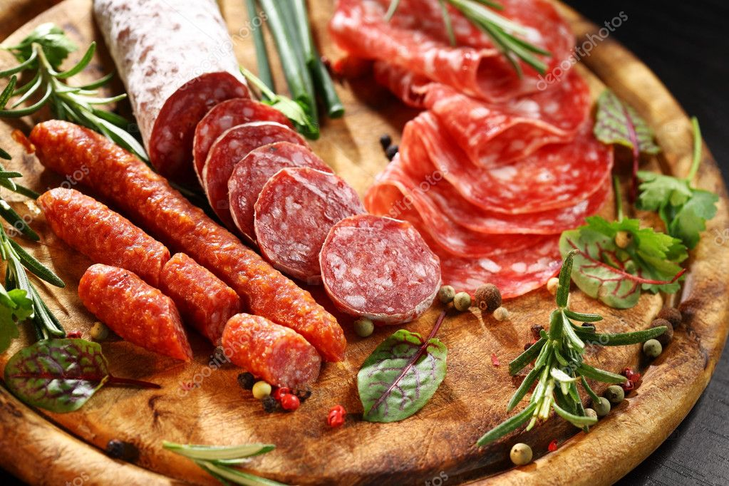 Different Italian ham and salami with herbs — Stock Photo #9902948