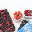 Stock Photo: Plastic containers of frozen mixed berries in snow - red currant, cranberry