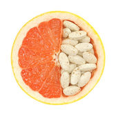Close up of red grapefruit and pills isolated - vitamin concept — Stock Photo