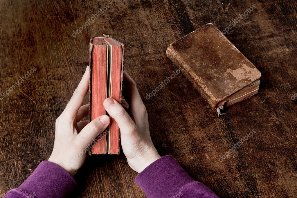 Very old book in hands - slightly open. with another one, closed, on the desk — Stock Photo #9124759