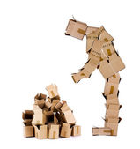 Box man looking at a pile of boxes — Stock Photo