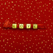Word of love beads on red velvet with sequins — Stock Photo #7969812