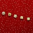 "Stock Photo: Word ""magic"" of beads on red velvet with sequins"