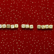 "Stock Photo: Phrase ""happy new year"" of beads on red velvet with sequins"