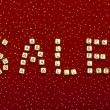 "Word ""SALE"" of beads on a red velvet with sequins — Stock Photo"