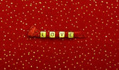 Word of love beads on red velvet with sequins — Stock Photo