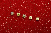 "The word ""magic"" of beads on a red velvet with sequins — Stock Photo"