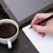 Closeup of a male hand writing notes on notepad — Stockfoto