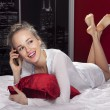 Woman lying on bed with smartphone l - Stock Photo