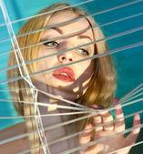 Kobieta patrząc przez żaluzje l — Zdjęcie stockowe