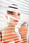 Frau suchen durch jalousie l — Stockfoto