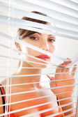 žena se dívá přes žaluzie l — Stock fotografie