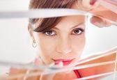 Kobieta patrząc przez żaluzje — Zdjęcie stockowe