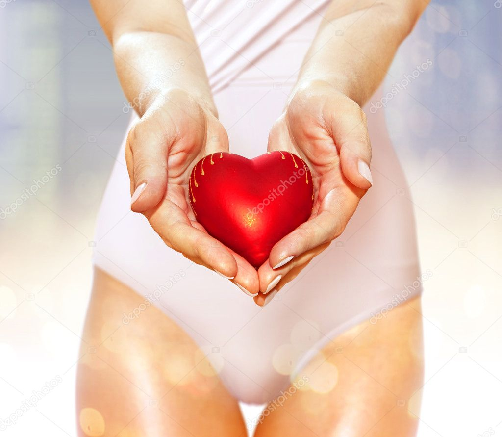 Artificial red heart on hands of beautiful woman  Stock Photo #8420817