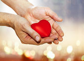 Artificial red heart on hands — Stock Photo
