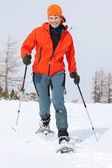 Young woman enjoying snowshoeing in sunny spring — Stock Photo
