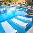 Tropical swimming pool with sunbeds — Stock Photo