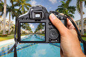 Camera in hand on tropical holidays — Stock Photo