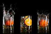 Splashing drinks with oranges — Stock Photo
