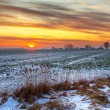 Idyllic sunset over snowy meadow - Stock Photo