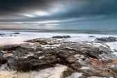 каменистый пейзаж на закате атлантического океана — Стоковое фото