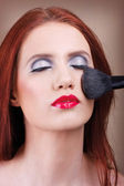 A make-up artist applying a make-up — Stock Photo