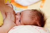 Baby girl sucking at her mother's breast — Stock Photo