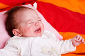 Baby girl lying on a soft blanket and crying — Stock Photo