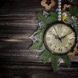 Foto de Stock  : Antique clock face with pearls, lace and firtree on the wooden b