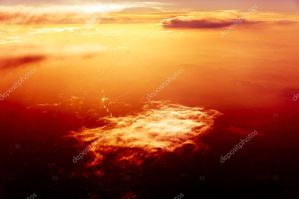 Dreamy view over the clouds at the sunset. Red background  Stock Photo #10051178