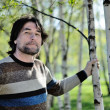 Middle-aged man in a birch grove — Stock Photo #10365206