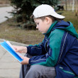 A boy reads a book on a park bench — Stock Photo