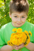 Boy with a bouquet of dandelions — Stock Photo