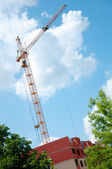 House under construction and tower crane — Stock Photo