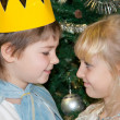 Boy and girl in carnival costumes for Christmas trees — Stock Photo