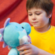 A boy with a soft toy dragon - a symbol of the new year — Stock Photo