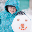 A boy and a snowman - a winter holiday — Stock Photo