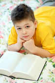 A boy reads a book in bed — Stock Photo