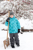 A boy with a wooden shovel for snow removal — Stock Photo
