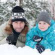 Dad and son rest in the snow in the park — Stock Photo