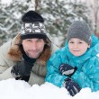 Dad and son rest in the snow in the park — Stock Photo #8593894
