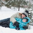 Dad and son rest in the snow in the park — Stock Photo #8593927