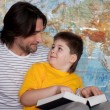 Dad and son reading a book on a map of the world — Stock Photo